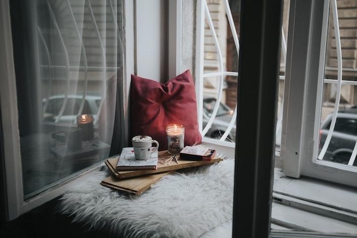 fond noel, de type hygge, un coussin d assise au bord d une fenêtre, plateau en bois avec livre, tasse de chocolat chaud et bougies romantique, coussin rouge