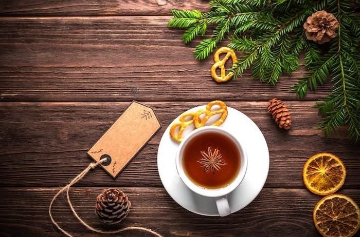 idée wallpaper noel en thé chaud dans une tasse blanche, pommes de pin, rondelles de citron, branches vertes de pin