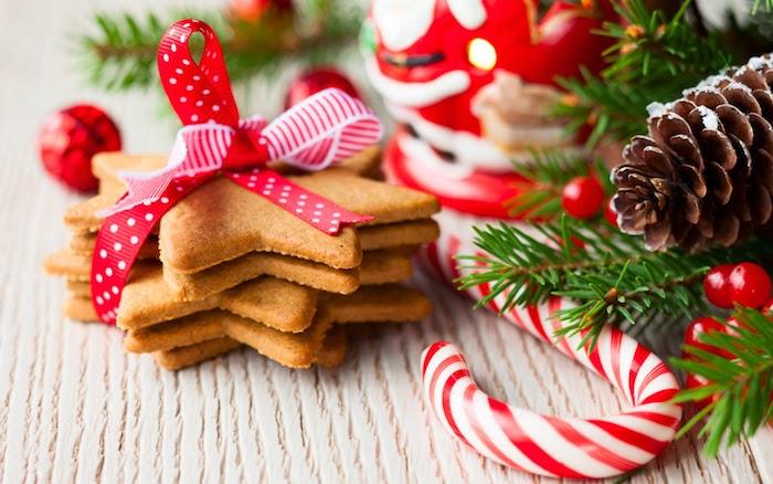 fond d écran noel gourmand, biscuits de noel, décorés de ruban rouge et blanc, branches de pin, houx, pommes de pin, canne de sucre et figurine pere noel