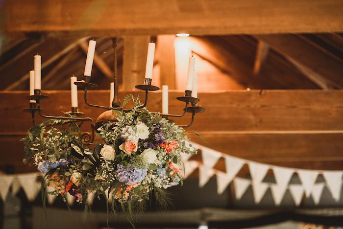 decoration mariage champetre de lustre baroque noire avec des bougies et deco de fleurs des champs
