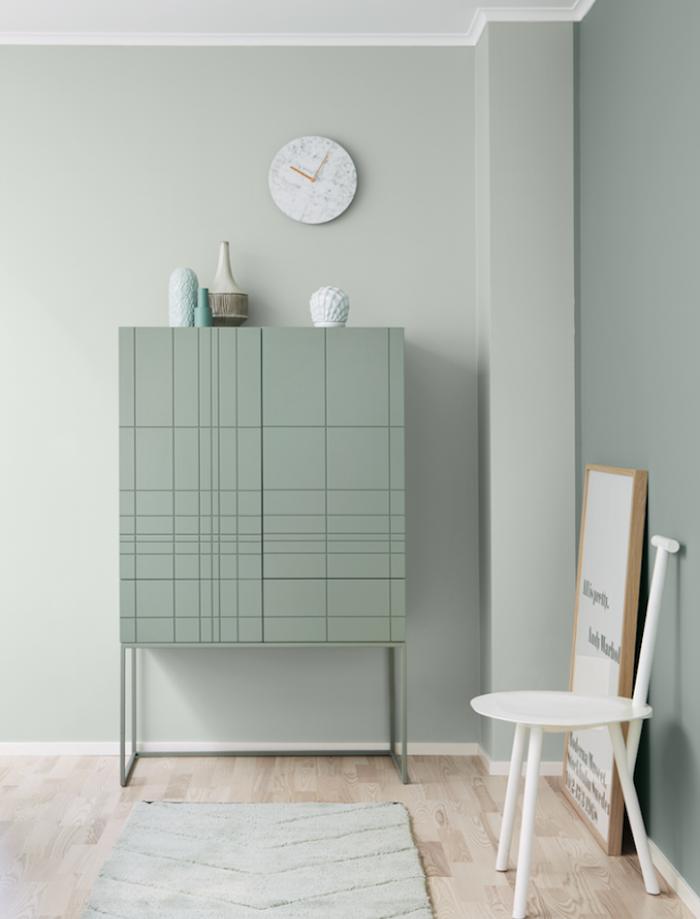 mur couleur bleu celadon, teinté de vert, et meuble vert gris, parquet clair, tapis gris, chaise blanche et cadre, tableau décoratif avec lettres noires sur un fond blanc
