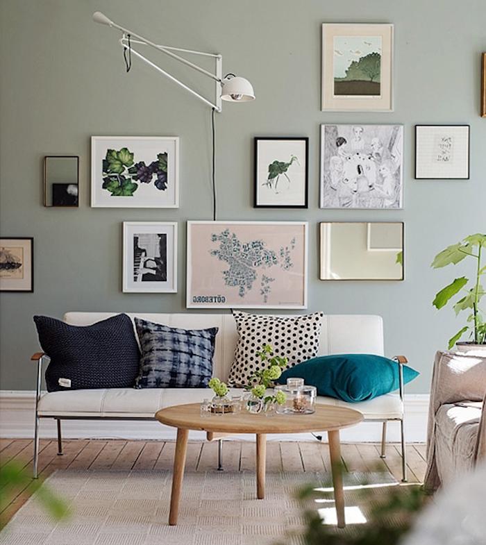 mur repeinte de couleur vert pastel, nuance céladon dans un salon design avec canapé ivoire, décoré de coussins bleu, gris et noir, table basse en bois, tapis gris clair, mur de cadres decoratifs, plantes vertes