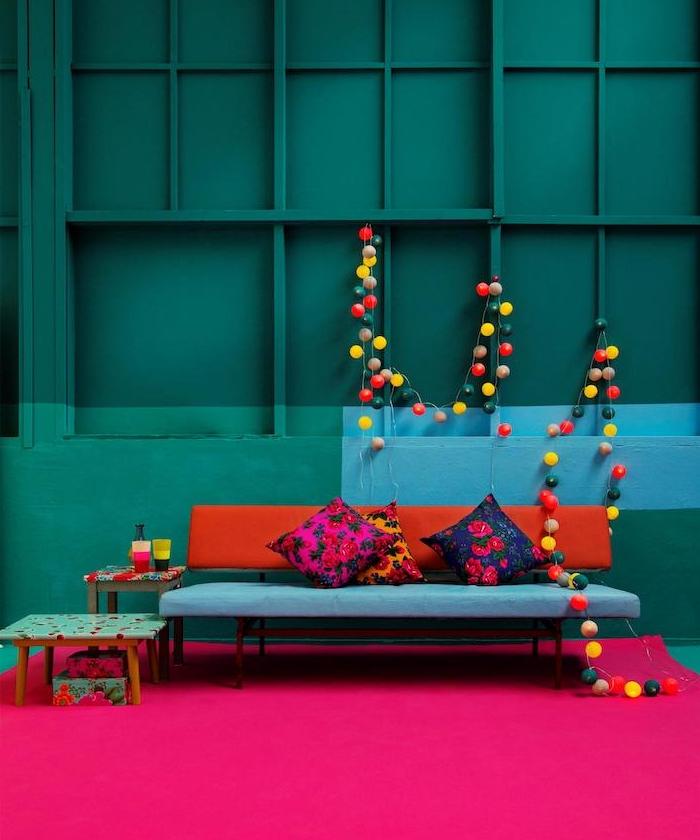 modele de salon bleu petrole, peinture murale nuance pétrole et paon, canapé design en bleu et rouge, tapis fuchsia, guirlande lumineuse colorée
