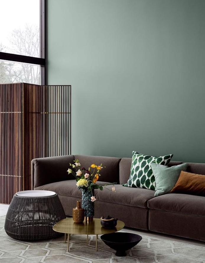 deco salon vert celadon, canapé gris anthracite. coussins vert et marron clair, table basse dorée, paravent en métal, bouquet de fleurs
