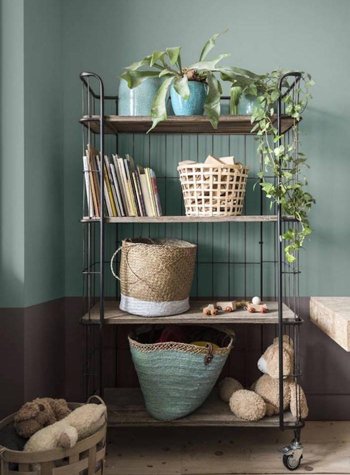 étagère en métal à roulettes avec de paniers, livres, plantes vertes, parquet en bois clair, table en bois rustique