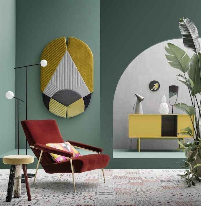 mur couleur vert de gris en combinaison avec des accents jaunes, revêtement sol en mosaique orientale, fauteuil rouge, plantes vertes, coussins à triangles colorés, commode jaune