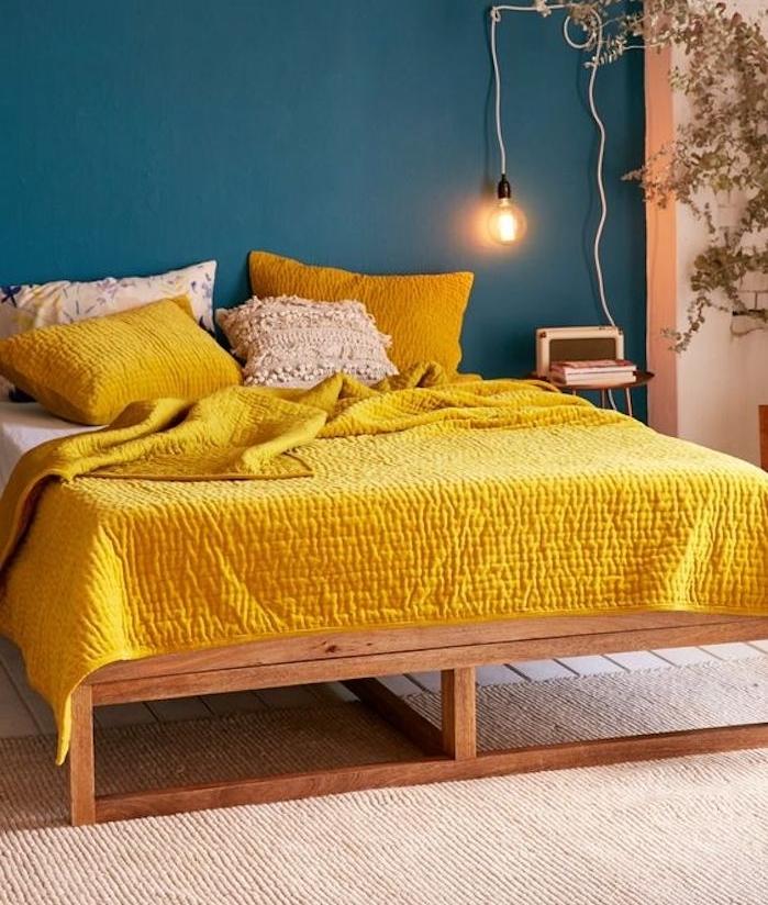 un pan de mur nuance de bleu, couleur pétrole, lit en bois, linge de lit blanc et jaune, lampe de nuit ampoule électrique, tapis beige, plante verte