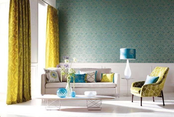 papier peint bleu petrole sur un pan de mur, canapé et table basse couleur blanche, sol blanc, rideaux jaunes baroques, petites touches de bleu turquoise