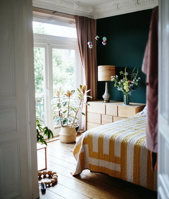 un seul pan de mur repeint de bleu petrole peinture, commode en bois, linge de lit blanc et jaune, parquet clair, plusieurs plantes vertes