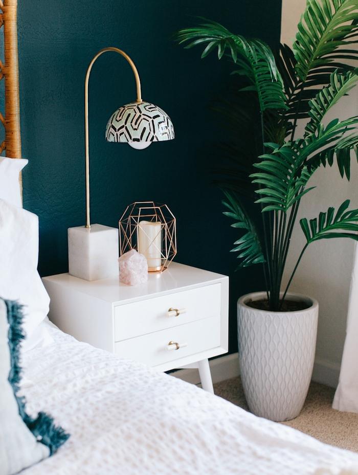 peinture chambre adulte couleur bleu canard, palmier vert, linge de lit blanc, table de nuit blanche, tapis gris, accessoires design