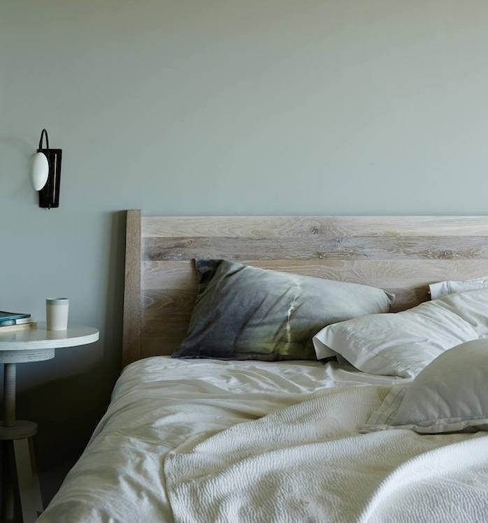 idée de peinture murale vert gris, lit en bois, linge de lit blanc, coussins gris, jaune et table en bois blanchie