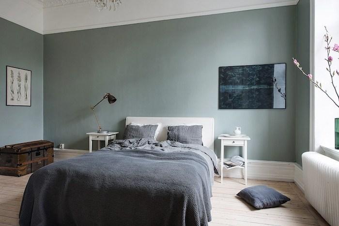 murs couleur vert de gris dans une chambre à coucher adulte design, parquet en bois clair, linge de lit gris, coffre de rangement vintage, chambre scandinave