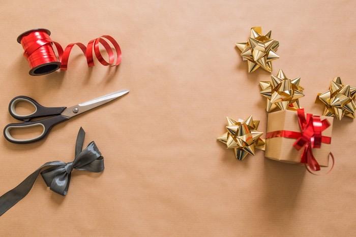fond d ecran de noel, projet diy emballage cadeau en papier craft, etoiles en papier dorées, ruban decoratif rouge, noeux noir et ciseaux