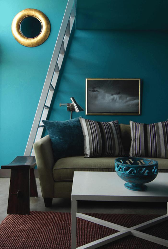 deco salon bleu canard comme choix de peinture murale, miroir rondm canapé vert olive, coussins canard, gris, noir et blanc, tapis rouge marron, table basse blanche