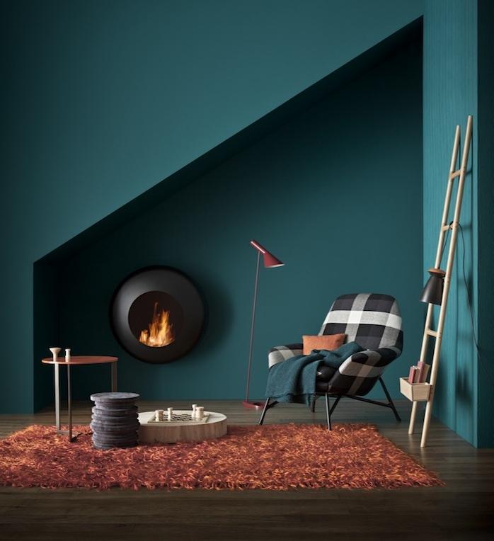 amenagement petit salon bleu petrole choisi comme couleur peinture, cheminée design noire, tapis rouge-marron, chaise noir et blanc, échelle en bois, parquet marron
