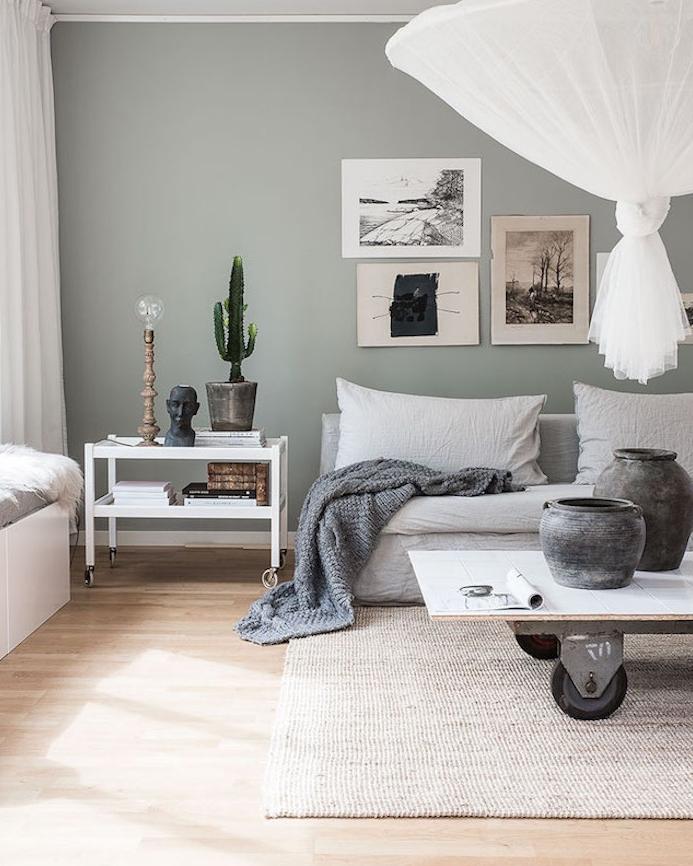 salon nordique avec canapé blanc cassé, table basse à roulettes, style industriel, tapis gris clair, couverture grise, suspension blanche originale et deco murale de dessins graphiques sur un mur couleur vert de gris céladon