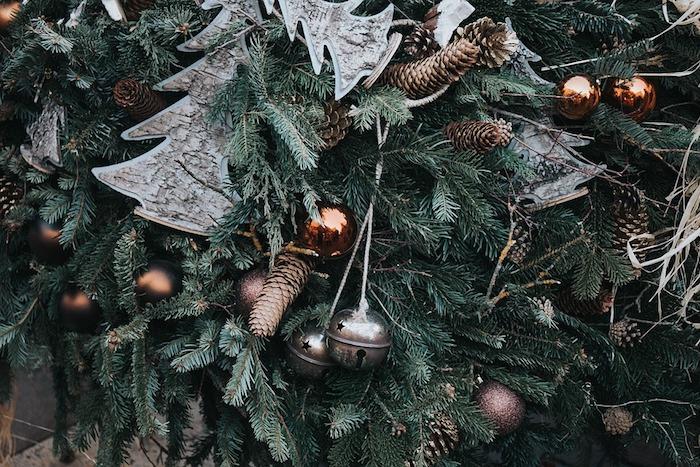 sapin de noel naturel avec decoration de pommes de pin, clochettes argentées, boules de noel cuivrées, petites figurines de sapins en écorce