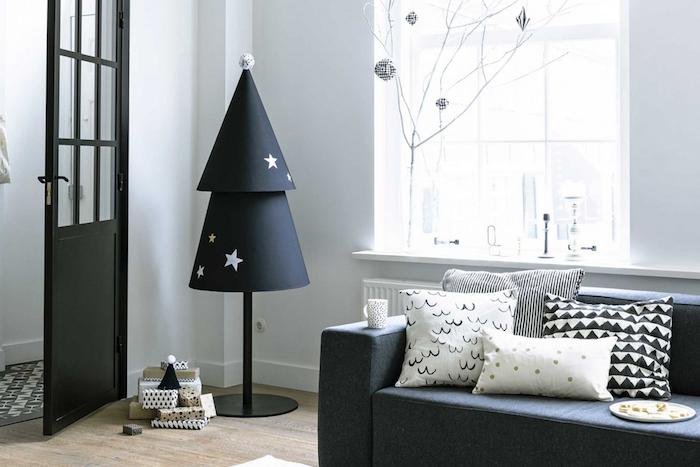 decoration sapin de noel en carton noir avec des étoiles blanches et or collées, parquet clair, canapé gris anthracite et coussins decoratifs noor et blanc