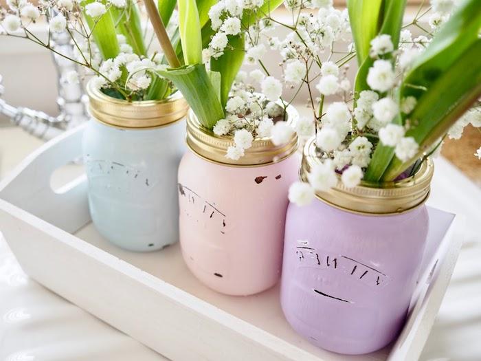 exemple de diy mariage, des pots en verre recyclés et repeints de couleurs pastel, fleurs blanches, cagette blanchie