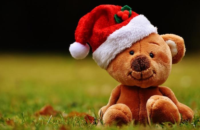 peluche ourson mignon avec chapeau de père noel rouge et blanc sur un gazon d herbe, fond ecran noel enfant