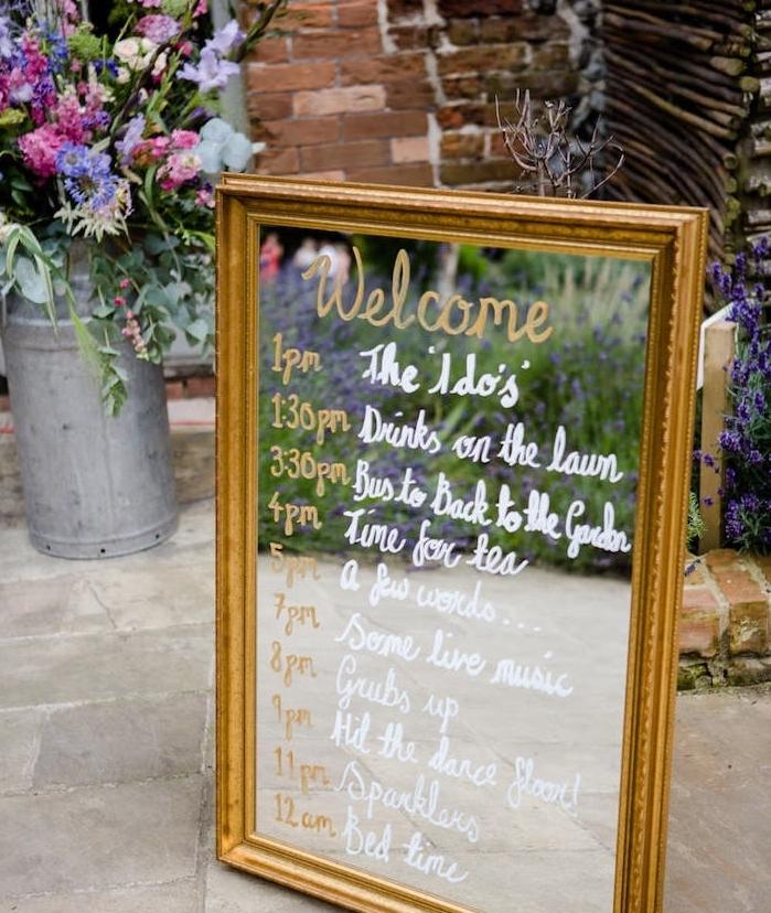 programme mariage écrit sur un miroir au feutre doré et blanc, decoration bouquet champetre dans un pot à lair