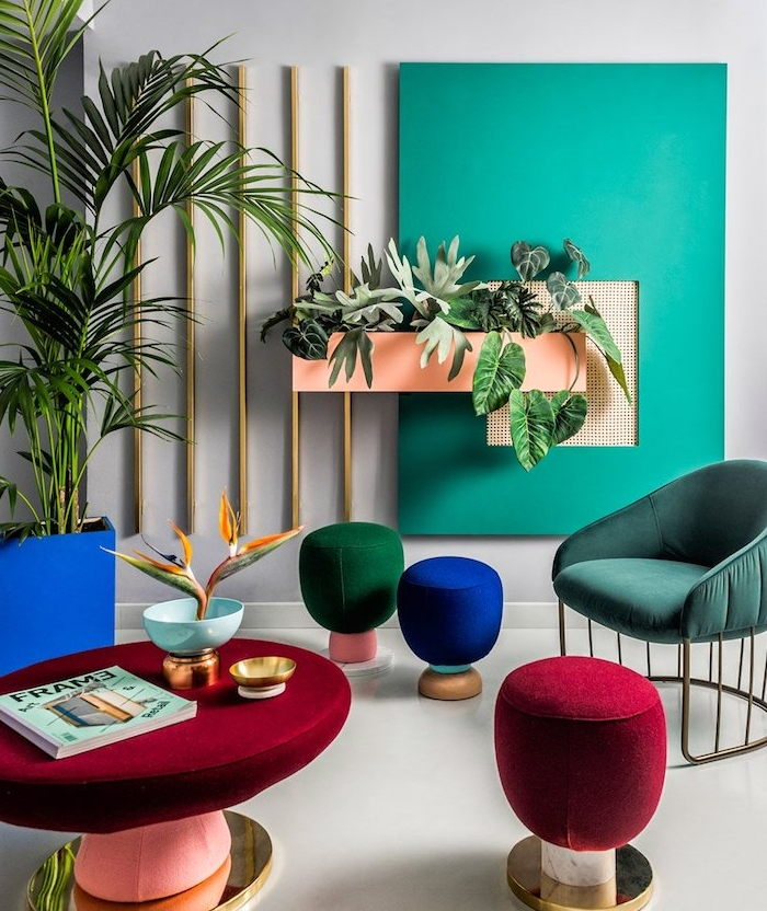 nuance de bleu, fauteuil teinte pétrole, tabourets design rouge, vert et bleu, table avec habillage rouge, plantes vertes, mur à carré vert turquoise