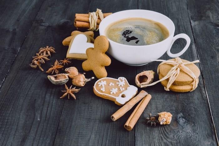 tasse de café blanche, sablés, biscuits, cannelle et noix sur une table en bois brut, wallpaper noel simple