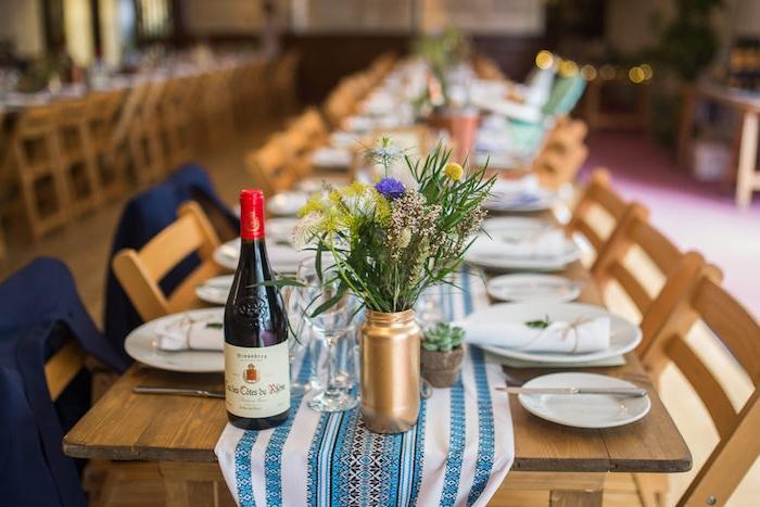 deco mariage champetre, vases repeints en peinture couleur or, bouquet champetre, chemin de table en bleu et blanc à motifs folkloriques sur une table en bois rustique