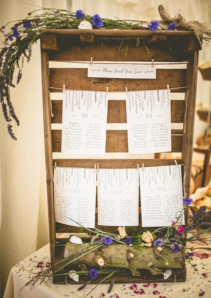 cagette bois décoration champêtre, buche de bois et fleurs champetre, listes blanches avec les noms des invités