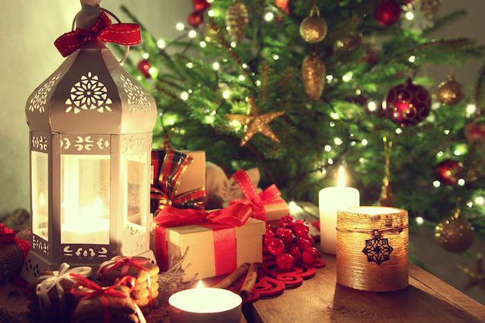 fonds d écran noel, table en bois décorée d une lanterne blanche, bougies romantiques, boites cadeaux parées de rubans rouges, biscuits et sapin de noel vert décoré