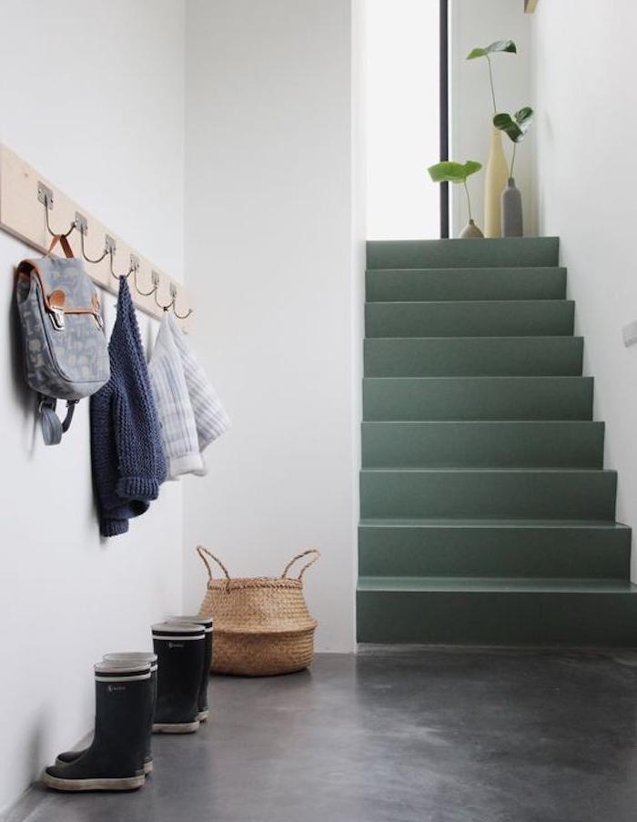 peinture escalier vert olive, sol effet béton, mur blanc et patère murale en bois avec des accroches, rangement vêtements, sacs à main, decoration de soliflores dans bouteilles en verre repeintes