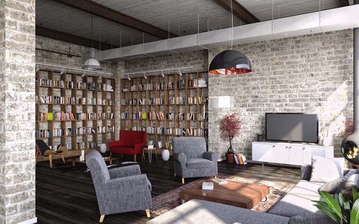 aménagement en style industriel, salon aux murs briques avec plancher noir et grande bibliothèque en bois clair