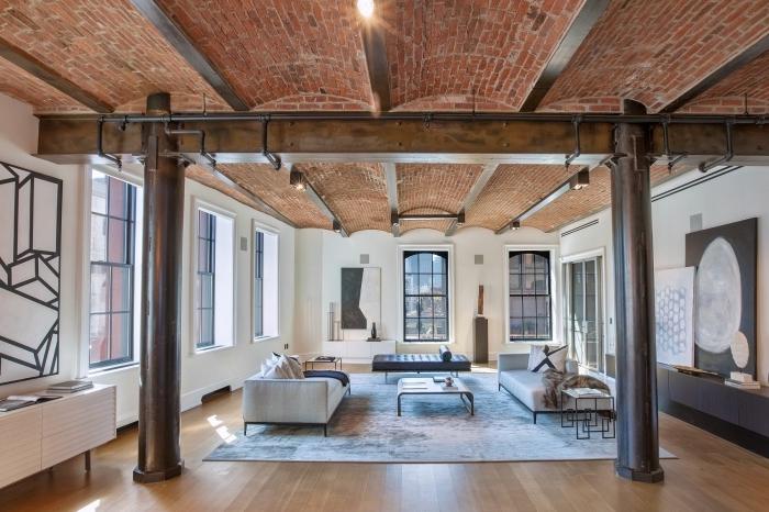 loft industriel, déco de salon aux murs blancs et plancher en bois, colonnes décoratives en bois et métal foncé