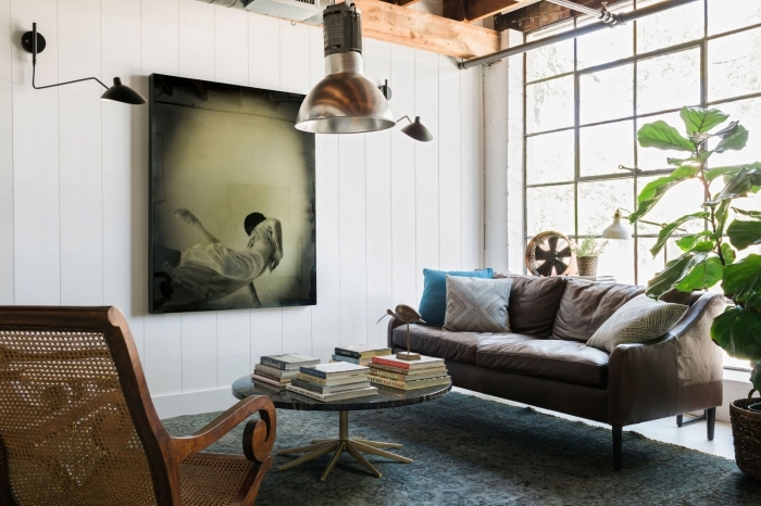 meuble style industriel, aménagement de salon loft aux murs blancs avec canapé en cuir marron et chaise en bois