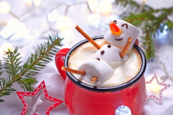 modele de fond d écran noel en tasse rouge de chocolat chaud, décoré de bonhomme de neige en guimauve, branches de pin, etoiles rouge et blanc, carte joyeux noel