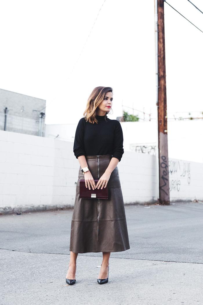 jupe mi-longue en cuir zippée devant en couleur kaki associée à un pull élégant en noir et un sac pochette bordeaux