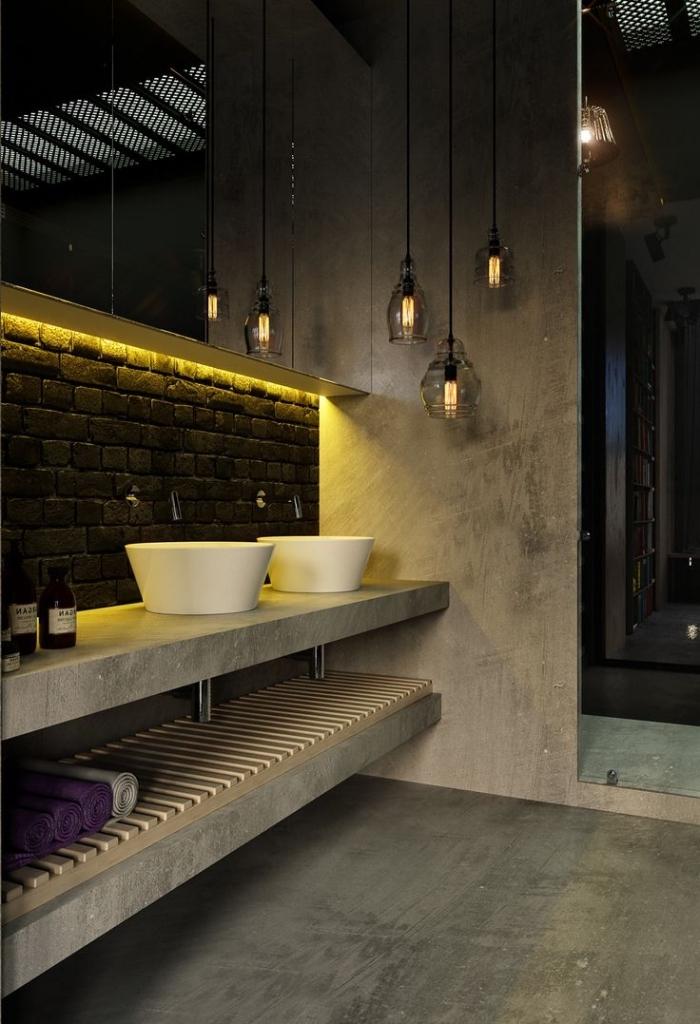 décoration de salle de bains en style loft, murs bétons avec déco en briques et éclairage led jaune