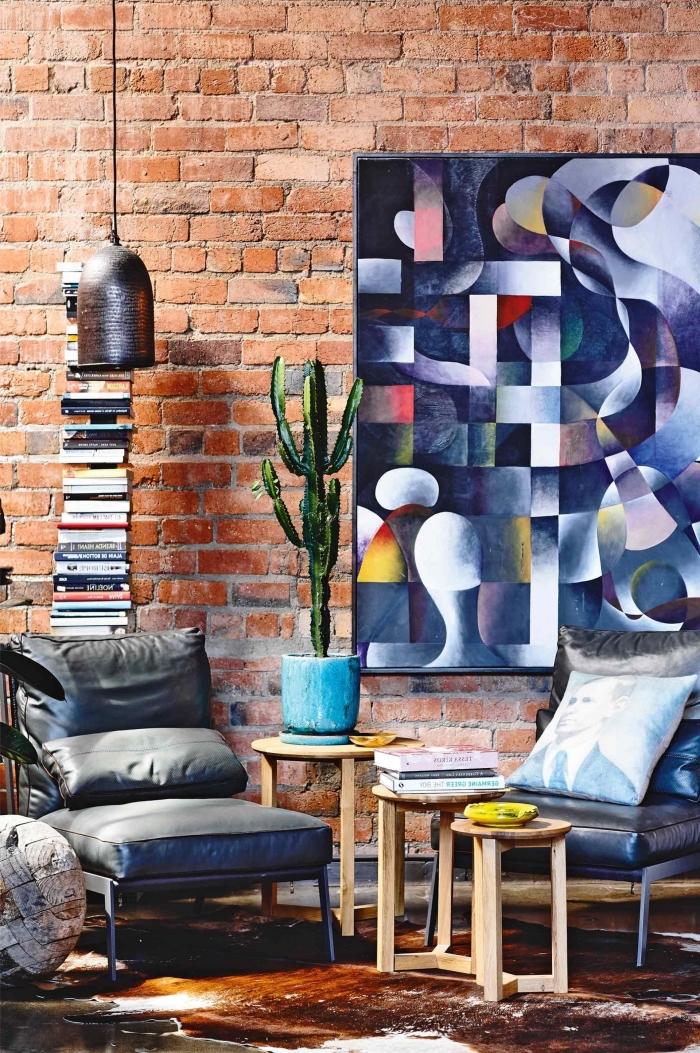 table basse industrielle, déco loft avec collection de livres, fauteuil en cuir foncé dans le salon aux murs briques