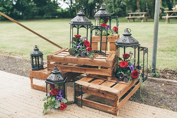 lanternes noires en metal avec des fleurs dedans, rangées autour de cagettes en bois, bouquet champetre de roses