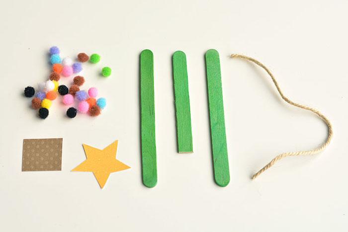 activité noel maternelle, matériaux nécessaires pour fabriquer un sapin de noel en batonnets de bois verts, decoration pompons et etoile en papier jaune