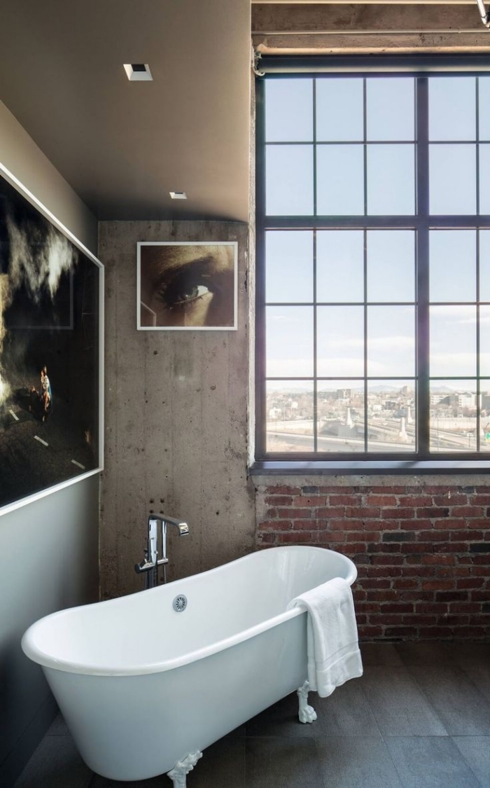 déco de salle de bain en style loft, revêtement murale en béton et briques rouges avec peintures aux cadres blancs