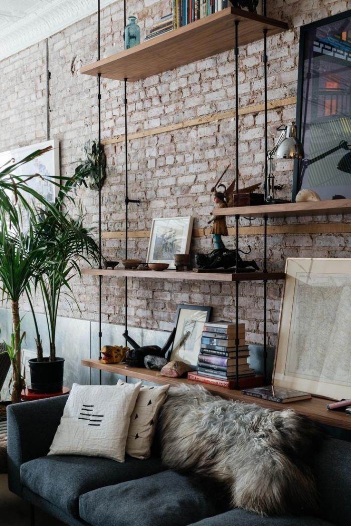 rangement verticale en bois, coussins décoratifs beige sur canapé en velours bleu foncé, plantes exotiques vertes dans pots noirs
