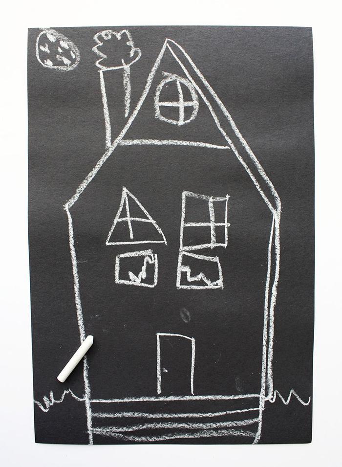 une activité manuelle automne pour réaliser une décoration d halloween avec les enfants, une maison hantée en papier cartonné noir dessinée à la craie
