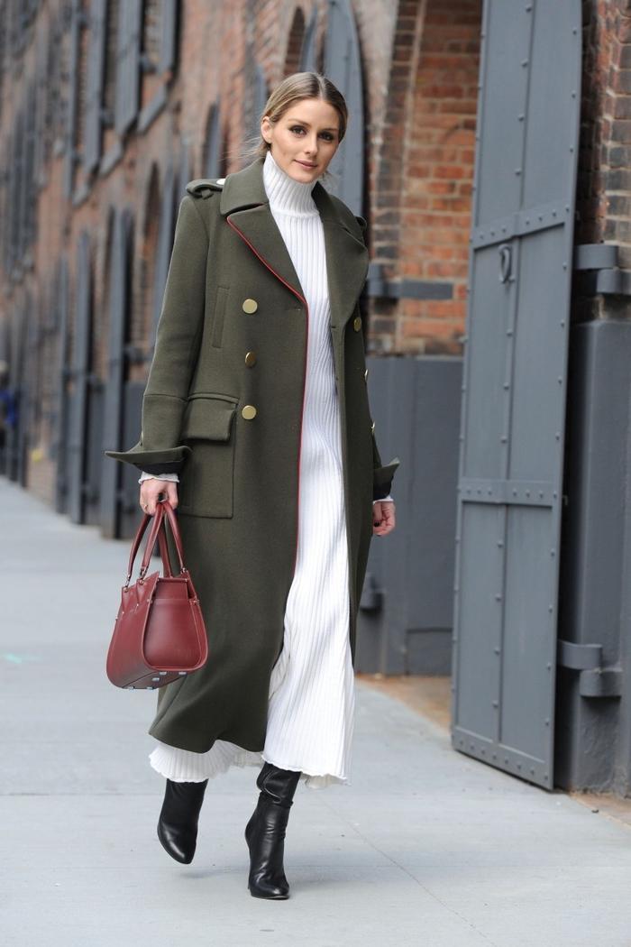 un manteau long femme de style militaire porté avec une maxi robe à col montant et des bottes noires en cuir pour une silhouette allongée et féminine