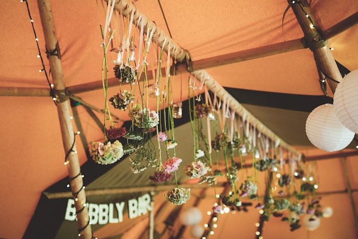 décoration champêtre, des fleurs suspendues par des rubans d'un poteau en bois, guirlandes lumineuses, lanternes blanches