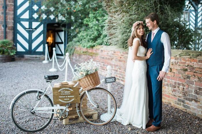 mariage champetre chic, velo vintage sur une palette en bois avec panier rustique avec fleurs champetre sur le guidon, couple mariée