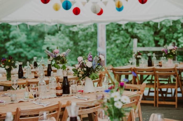 table et chaises en bois, deco mariage champetre, brocs avec des bouquets de fleurs, suspensions origami boules colorées