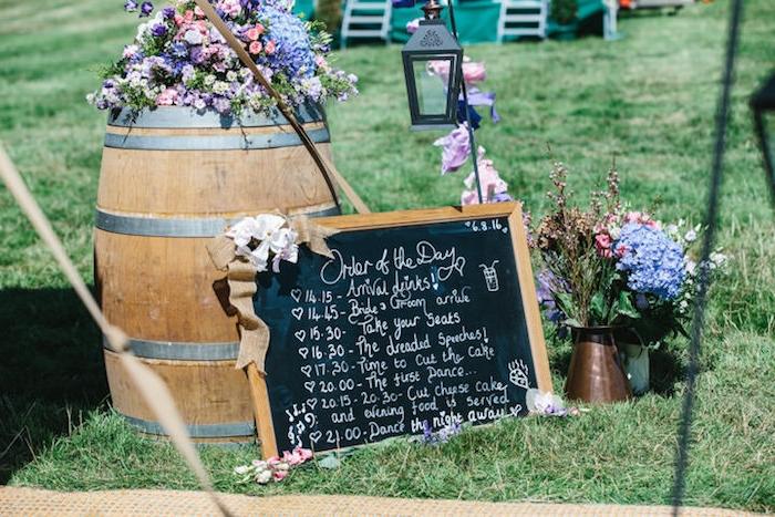 bouquet champetre dans un broc et tonneau en bois fleuri, tableau noir avec programme mariage écrit à la craie, lanterne noire