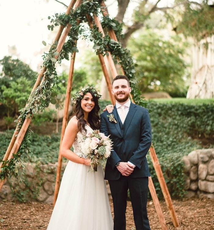 diy mariage, style champetre, tipi en bois avec decoration de guirlande feuillage verte, femme en robe champetre et bouquet de fleurs