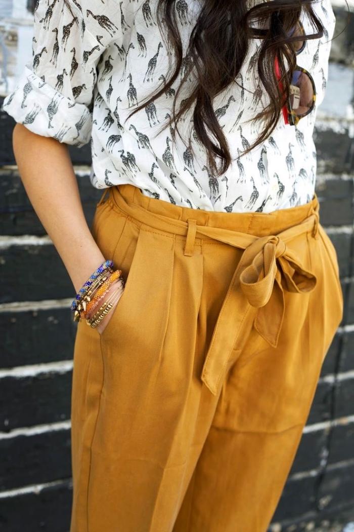 couleurs neutres dans la mode, blouse blanche à girafes noirs avec pantalon camel et bracelets